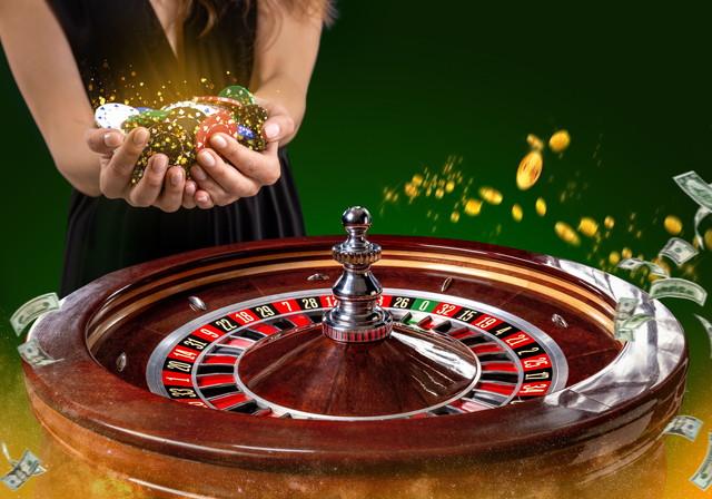 女性の手でポーカーチップと色とりどりのカジノルーレットテーブルのクローズアップ