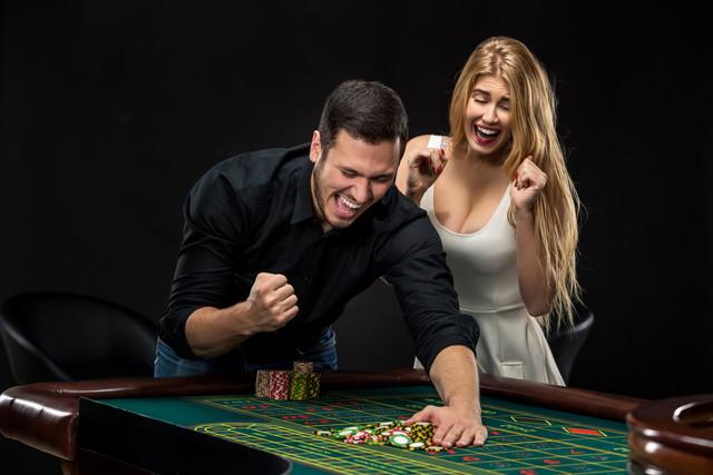 カジノのルーレットのテーブルで勝利を祝っている若いカップル