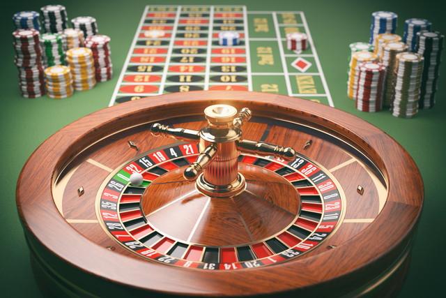 緑色のテーブル上のカジノチップを搭載したカジノルーレット盤