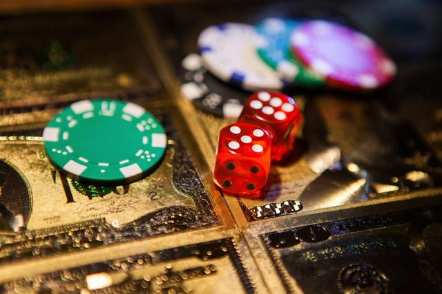 カジノ赤サイコロと黄金の米ドル紙幣の背景にカジノポーカーチップ