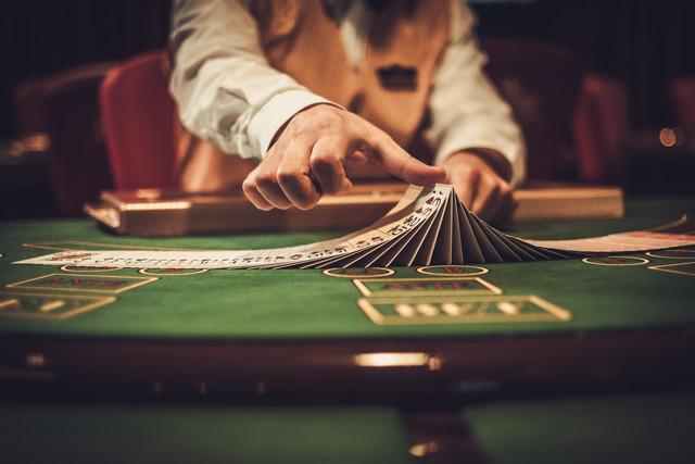 カジノでギャンブルテーブルの後ろにクルーピア