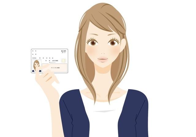 マイナンバーカードを見せる女性