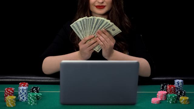 パソコンの前で札を持っている女性