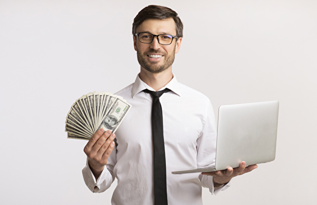 札とパソコンを持って喜ぶ男性