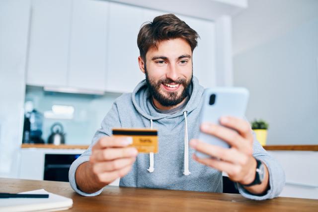 クレジットカードとスマホを持つ男性